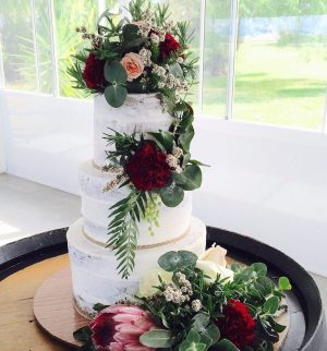 Rustic wedding cake adorned with bohemian burgundy flowers styled by Willa Floral Design