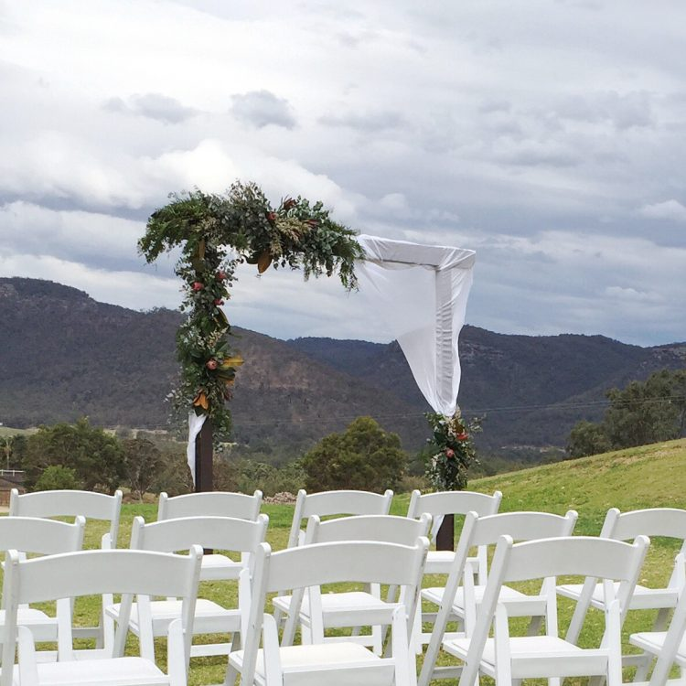 Wedding ceremony arbour florals by Willa Floral Design featuring lush foliage at Adams Peak Estate